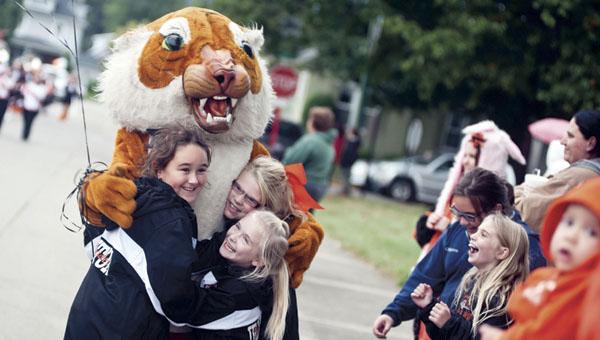 Taylor Vanderhoof, Emily York and Daizy Meadows give the Ironton High School Tiger mascot a big hug during the first homecoming parade Thursday along Bob Lutz Way.