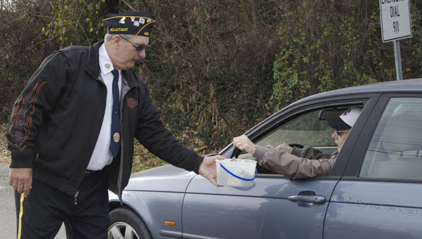 Bill Caines, above, adjutant for American Legion Post 433 in Ironton, collects donations on Friday to assist veterans in Lawrence County nursing homes.
