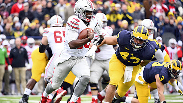 Ohio State Buckeyes' quarterback J.T. Barrett (16) outruns Michigan Wolverines defensive end Chris Wormley (43) to gain yardage during the first quarter of Saturday's game. Ohio State won 42-13. (Tim Fuller of USA TODAY/Courtesy Ohio State Athletics.com)