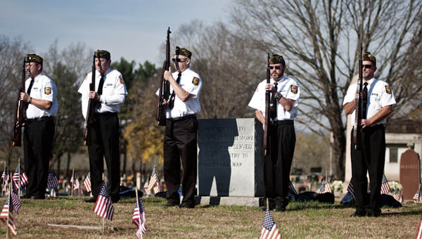 Members of the VFW 8850, Ironton Post, stand at attention. (BELOW) Rob Curnell holds the flag during the Veterans Day service at Woodland Cemetery on Wednesday.