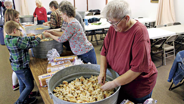 Deb Hagerty (front right) and other volunteers break up bread Wednesday at the Ironton City Mission to prepare for its Thanksgiving dinner.