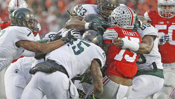 Ohio State running back Ezekiel Elliott (15) is tackled by a host of Michigan State Spartans in the first half last Saturday at Ohio Stadium in Columbus. Michigan State won, 17-14. The Buckeyes visit rival Michigan this Saturday. (Brooke LaValley/Columbus Dispatch/TNS.MCT Direct Photo)