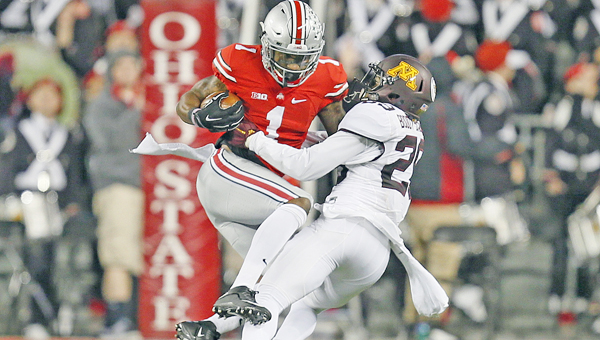 Ohio State wide receiver Braxton Miller (1) is taken down by Minnesota defensive back Briean Boddy-Calhoun (29), and gets injured in the process, in the fourth quarter at Ohio Stadium in Columbus, Ohio, on Saturday. The host Buckeyes won, 28-14. (Eamon Queeney/Columbus Dispatch/TNS)