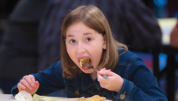Twelve-year-old Emma Randan, of Proctorville, takes a mouthful of pancakes while at the annual Chesapeake-Proctorville Lions Club pancake breakfast on Saturday.