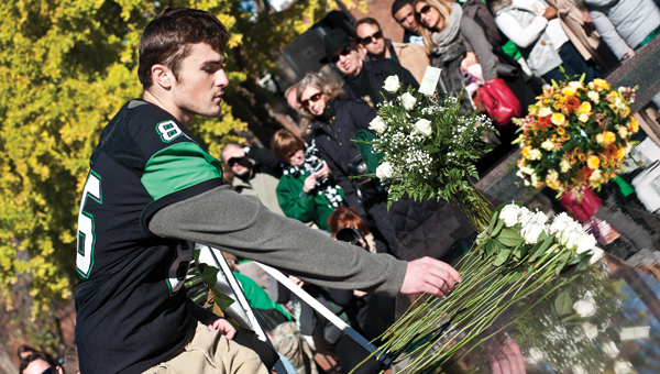Marshall University students lay white roses along the edge of the school's fountain, one rose each for of the 75 lives lost in a plane crash in 1970, during the annual memorial service on Saturday.