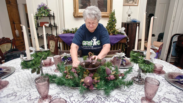 Gail Webb prepares the dining room of the Lawrence County Museum in preparation for the Christmas holiday season.