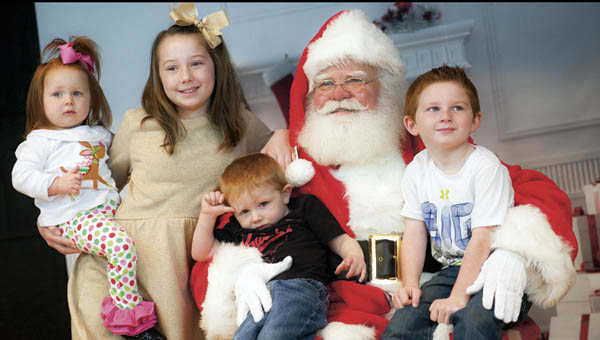 Rowe family children, pictured left to right, are Maizleigh, Kayleigh, Wyler and Tucker, sit on Santa's lap at the Breakfast with Santa on Saturday.