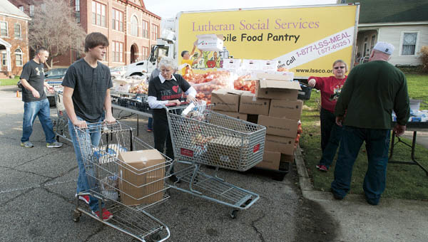 Volunteers gathered on Center Street next to St. Paul Lutheran Church to help with Christmas with Dignity on Saturday in Ironton.