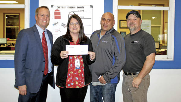 David Sheils, president of the St. Mary's Foundation, and Anne Hammack, clinical manager of the St. Mary's Breast Center, receive a check from Holland's Miguel Celdran, plant manager, and Terry Lucas, strap department manager.