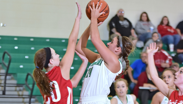 Fairland Lady Dragons' Taylor Perry (24) takes aim with a shot as Rock Hill Redwomen's Samantha Dillon (20) attempts to block the shot. Fairland opened the season with a 75-33 Ohio Valley Conference win on Thursday. (Kent Sanborn of Southern Ohio Sports Photos)