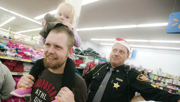 Bryzlyn Burke rides on daddy, Greg Burke's, shoulders while shopping with Deputy Todd Easterling.