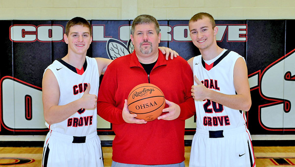 Coal Grove Hornets' first-year head basketball coach Kevin Vanderhoof (center) is flanked by seniors Cole Gannon (3) and Dalton Miller (20). The Hornets beat Gallipolis 60-53 on Tuesday to give Vanderhoof his first career win. (Kent Sanborn of Southern Ohio Sports Photos.com)