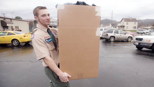 Wyatt Boggs, with Boy Scout Troop 106, helps deliver boxed goods to cars during a giveaway event at the City Welfare Mission Wednesday in Ironton.