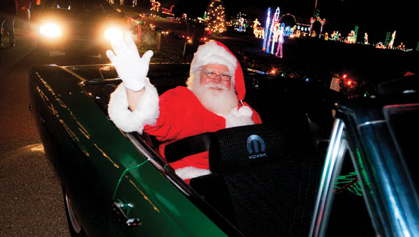 Santa Claus makes an appearance at the Coal Grove Christmas Parade riding in a Plymouth convertible Friday evening.