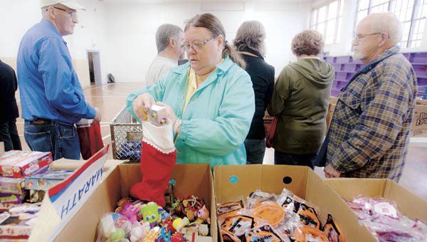 Alma Booth volunteers with the Community Mission Outreach on Friday at the Chesapeake Community Center filling stockings and bags to be given to local children.