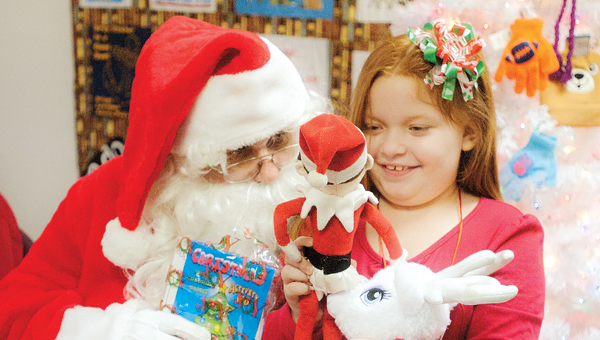 Lilly Bowman shows off her Elf on the Shelf while visiting with Santa Claus at the Briggs Lawrence County Library Chesapeake Branch Tuesday evening.
