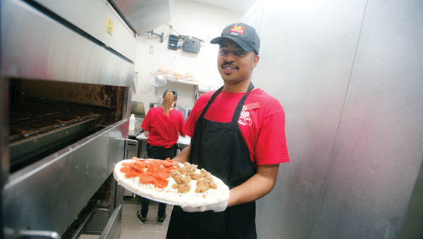 "Kenerick ""Smiley"" Jones prepares to insert a pizza into the oven at the new Marco's restaurant in downtown Ironton."