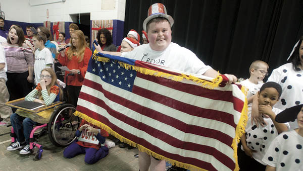 """Trevor Hall stands proudly holding the American flag as students and faculty perform """"Let There Be Peace On Earth"""" for the finale of the Open Door School """"A Disney Christmas"""" on Tuesday."""