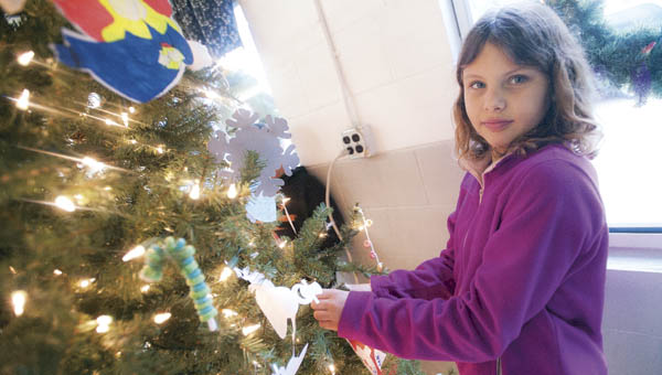 Angela Stapleton, with Lee Ann Cremeans' fifth grade class, helps to decorate the Christmas tree at the H. Jae Roush Community Building in Coal Grove Tuesday morning.