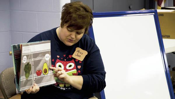Library assistant Jan Gullett reads to children.