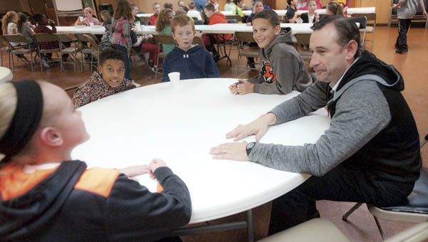 Pastor Eric Barnes, with the First Baptist Church in Ironton, sits with local youth during snack time at the after school program Thursday.