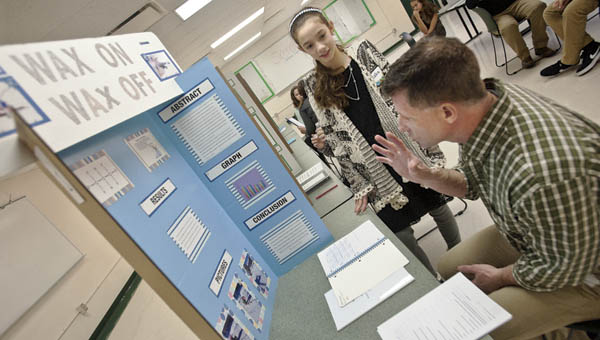"""Judge Dan Webb speaks with student Blake Anderson on his project of """"Wax On Wax Off"""" at the Fairland Middle School science fair Wednesday."""