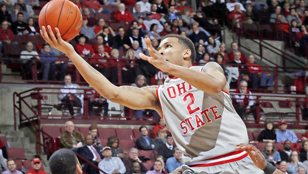 Ohio State forward Marc Loving (2) leaps over Penn State guard Shep Garner (33) to score two points during the second half on Monday at Value City Arena in Columbus, Ohio. (Brooke LaValley/Columbus Dispatch/TNS)