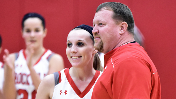 Rock Hill Redwomen senior Kaci Russell is presented the game ball by coach Greg Damron after she scored her 1,000th career point on Monday in a 65-31 win over Portsmouth. (Kent Sanborn of Southern Ohio Sports Photos)