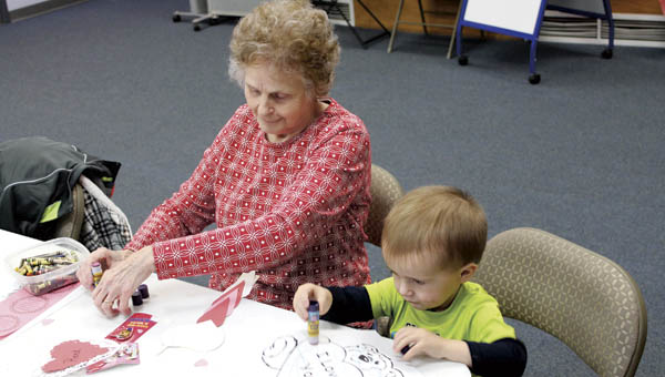 Reed Craft, 2, and his grandma work on Valentine's Day crafts during Ironton Briggs Library toddler time Tuesday morning.