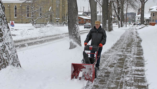 St. Lawrence School janitor Jim Monte snow blows the sidewalk in front of the school along Sixth Street in Ironton on Monday morning.