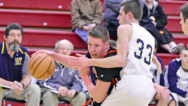 Coal Grove Hornets' Jeb Jones (with ball) drives toward the basket as Wellston's Caden Ervin (33) attempts to stop his efforts. Coal Grove lost 52-44 in the Division III sectional tournament on Monday at Jackson. (Kent Sanborn of Southern Ohio Sports Photos)