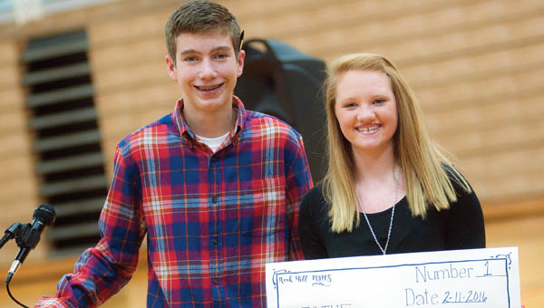 Students Brady Floyd, left, and Raiden Jenkins, right, present a check for $1,000 to the Junior Diabetes  Research Foundation.