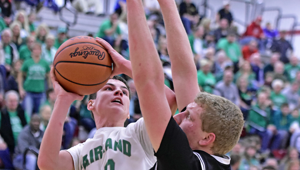 Fairland Dragons' Gunner Short (52) scores inside against Oak Hill's Dennis Fleming (50) during the Division III sectional finals on Friday. Fairland won 52-47 and will play in the district semifinals next Sunday in Athens. (Kent Sanborn of Southern Ohio Sports Photos)