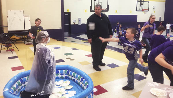 Asher Maynard, a student at Chesapeake Elementary, throws a pie at his principal, Trisha Harris, on Friday, as part of the school's Read Across America Week activities.