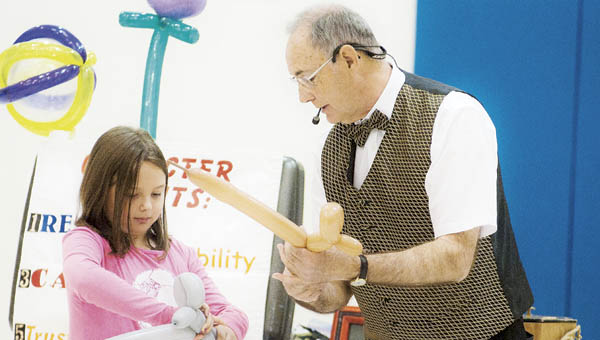 Second grade student Lily Stewart makes a balloon dog with magician Garry Boothe during a performance at Burlington Elementary School on Thursday.