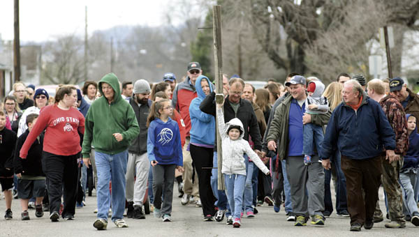 Members of Sharon Baptist Church make their annual pilgrimage down South Fourth Street to Woodland Cemetery carrying a wooden cross on Good Friday.