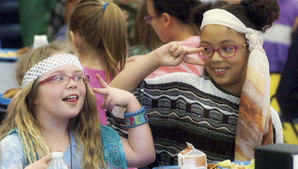 """Hannah Gillum, left, and Kyra Taylor, right, is feeling groovy as they eat their lunch Tuesday and dance to the music at South Point Elementary. Students and faculty were encouraged to dress up in a groovy fashion for the book fair themed """"Feeling Groovy About Books."""""""