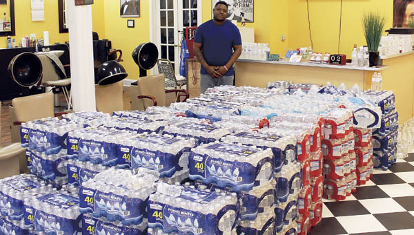 Antonio Murphy, owner of Only 1st Impressions barbershop, stands with cases of water donated for the people of Flint, Michigan. The shop started collecting water for Flint on Monday of last week.