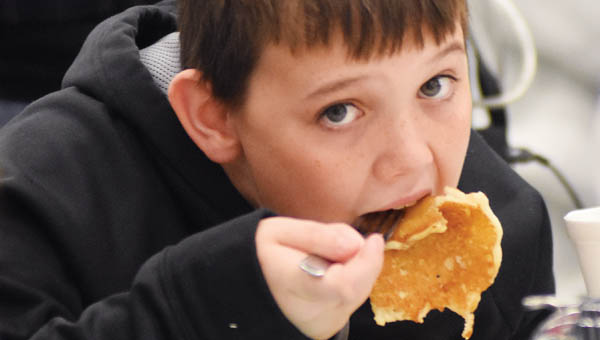 Tanner Moore eats pancakes and sausage during the annual Coal Grove Lions Club Pancake Breakfast event Saturday at the Dawson-Bryant High School.