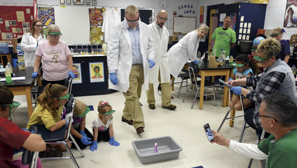 Participants take part in a chemistry class by making elephant toothpaste during Family Science Night at Chesapeake Middle School.