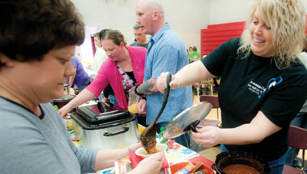 Megan Chaffin, with Community Home Health Care, serves homemade chili during the annual Chili Fest and Craft Show for DD Awareness Saturday at Dawson-Bryant High School.