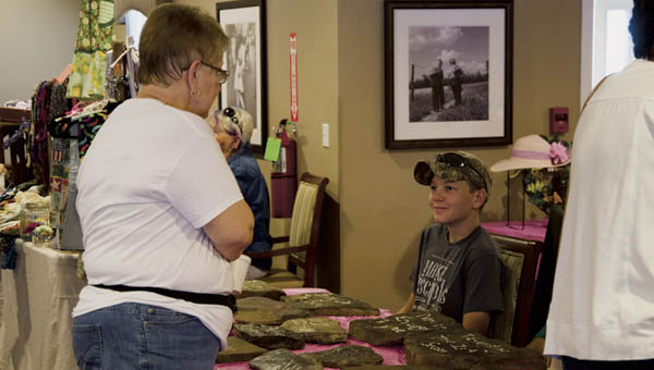 Caleb Miller of South Point was selling plaques made from creek bed rocks at the farmers market and craft sale at the Wyngate at RiversEdge in Rome Township on Saturday.