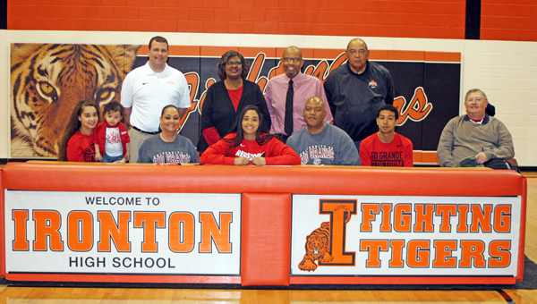 Ironton Lady Fighting Tigers' senior basketball standout Cheyenne Scott signed a letter-of-intent with the University of Rio Grande on Friday. Attending the ceremony were: seated left to right, sister Chantelle Crockrel, nephew Kingston Crockrel, mother Angie Scott, Cheyenne, father Charles Scott II, brother Charles Scott III, and Rev. Calvin A. Bradley Jr., pastor of Christ Temple; standing left to right, Ironton head coach Doug Graham, great-aunt Annette Scott, great uncle Hugh Donald Scott, and coach Dan Pride. (Photo Courtesy Kristina Billings of Ironton High School)