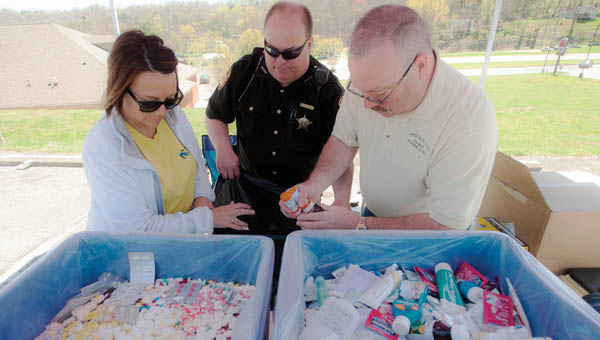 Stephanie Helms, left, and Steve Hileman, right, with the Lawrence Scioto Solid Waste Management District and Lawrence County Sheriff's Deputy John Majher, center, dispose of dropped off drugs during a drug take back program at Ironton Hills Plaza Saturday.