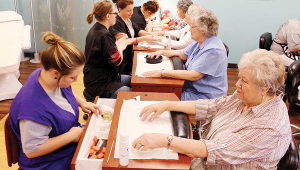A group of women get manicures Friday at Collins Career Center Senior Citizens Day.