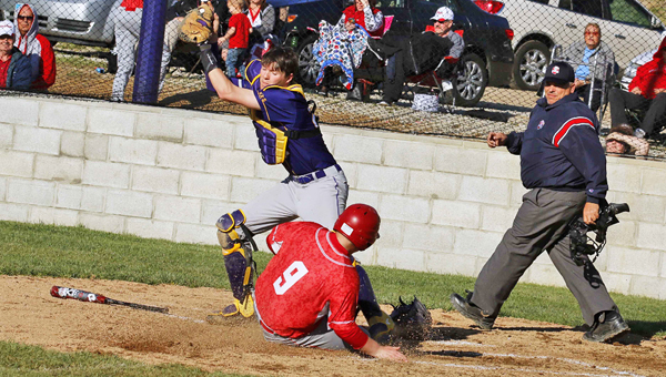 St. Joseph Flyers' catcher Zac McGraw reaches for a throw as Rock Hill's Kaleb Kidd (9) slides across home plate to score a run. The Redmen beat the Flyers 10-0. (Tim Gearhart of Tim's News & Novelties, Park Ave. in Ironton)
