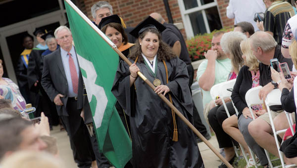 Nicole Pappas Mollica carries the flag representing Ohio University Southern at the start of the graduation program on Friday.