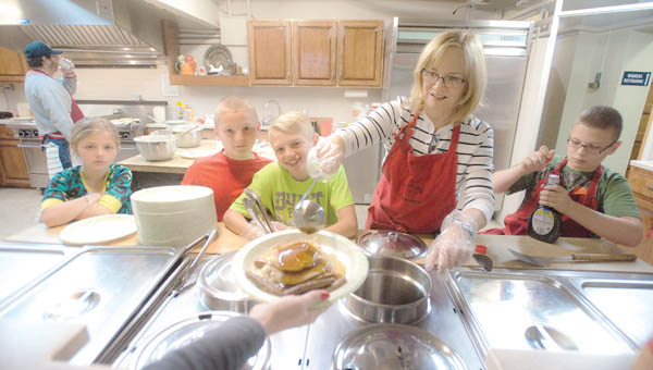 The Gleichauf clan, pictured left to right, McKenzie, Morgan, Mick, Patty and Max, help to serve up breakfast during the annual pancake breakfast Saturday morning at the First United Methodist Church in Ironton.