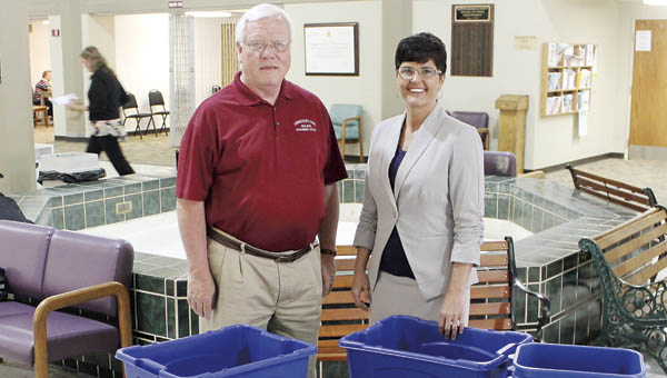Dan Palmer, Scioto-Lawrence Solid Waste Management District coordinator, and Ironton Mayor Katrina Keith stand with the new recycling containers the Ironton City Center has received. The center is one of the newest recycling locations for the solid waste district.