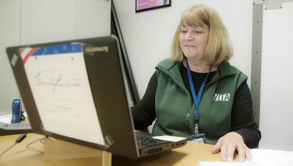Kathy Moore, site coordinator for VITA, reviews tax documents Tuesday at the Ohio Means Jobs in Ironton.